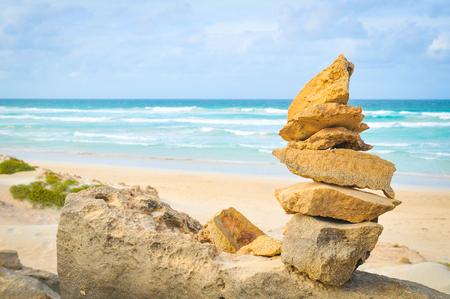 Bringen Sie Ihr Leben, Ihre Meditation, Ihre Achtsamkeit oder Ihr Zen-Konzept mit Steinen in Einklang, die am Meer aufgestapelt sind Standard-Bild