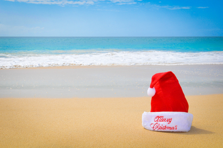 Travel or holiday concept with a detail of a red Santa hat on an exotic beach