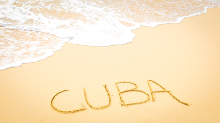 Visit Cuba concept written on the sand of an exotic beach
