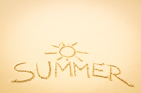 Summer concept written on the sand of an exotic beach