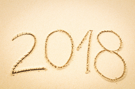 Year 2018 written on the sand of an exotic beach