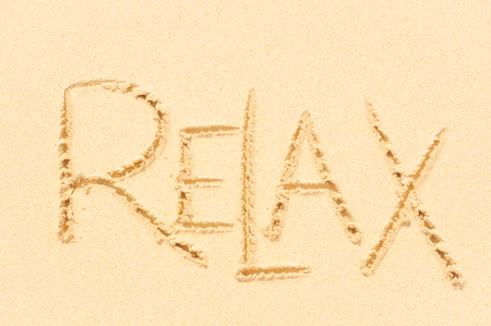 Relaxation concept written on the sand of an exotic beach