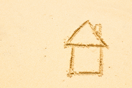 Home insurance concept with a house drawn on the beach