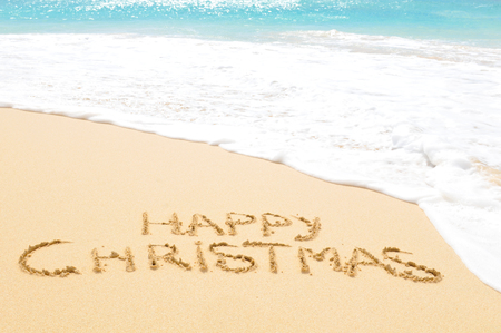 Happy Christmas written on sand of an exotic beach
