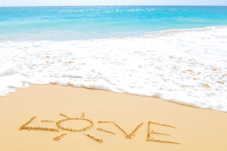 Love written on the sand of an exotic beach