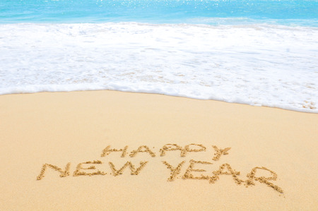 Happy New Year written on sand of an exotic beach