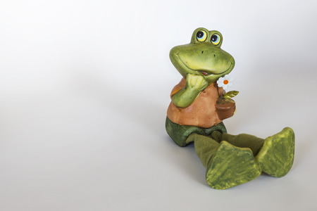 Ceramic statue of cheerful Frog with flower photo