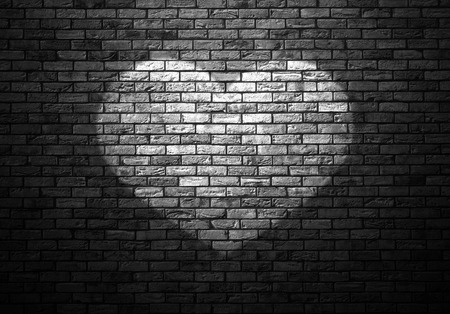dimly: dimly lit old brick wall enlightened cone of light in the shape of heart