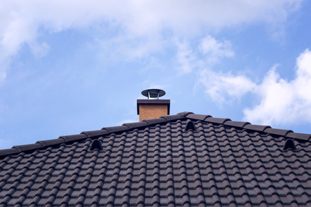 Orange chimney on tiled roof