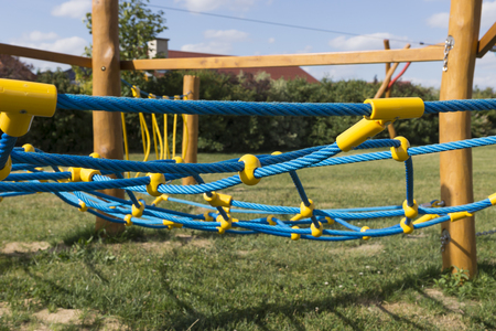 climbing frames: yellow and blue rope-climbing frame in the playground Stock Photo