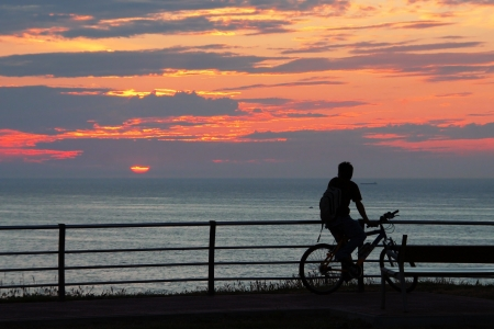 biker man resting and seeing at the sunset