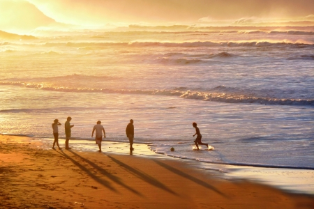 people playing soccer in the beach at sunset photo