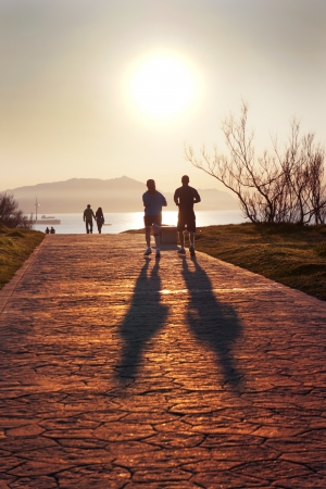 silhouette of people jogging and walking in Getxo park at sunset