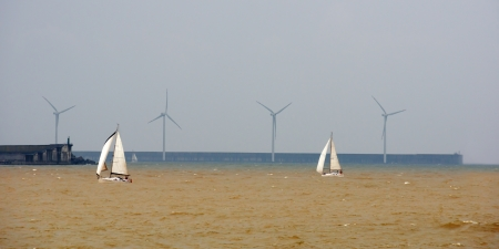 Sailboats in rough sea and a wind farm photo