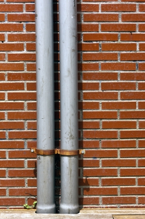drainpipe on a wall with bricks