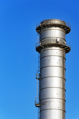 metallic smokestack with stairs against blue sky photo