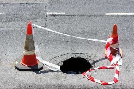 road hole with warning cones and tape photo