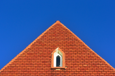 window in a roof attic with bricks against blue sky with triangle shape photo