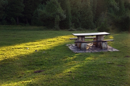 picnic table on countryside with sun beams on grass