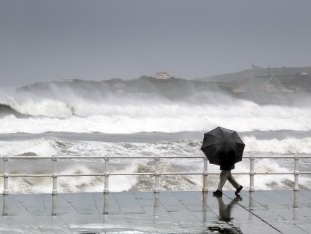 wzburzone morze: Osoba ochrony z parasolem w deszczowy i wietrzny dzień chodzenia po promenadzie z wzburzonym morzu