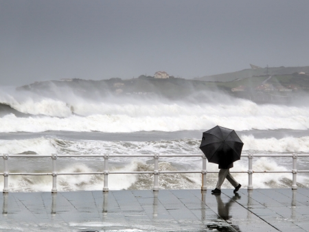 person protecting with umbrella in rainy and windy day walking on promenade with rough sea