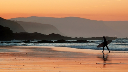 surfer on beach shore at sunset