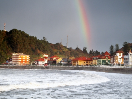 Ribadadesella promenade with waves, stormy weather and a rainbow photo