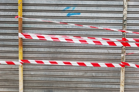 metallic shutter door closed with caution tape Stock Photo - 25316718