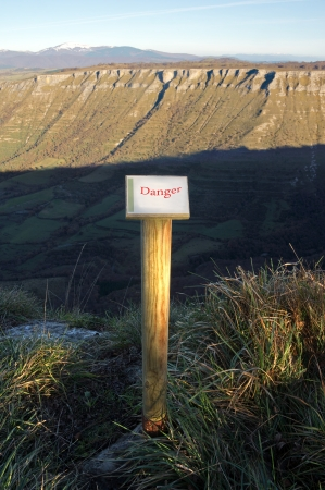 steep cliffs sign: wooden post with danger sign on mountain cliff Stock Photo