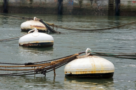buoys: rusty buoys in port water with ropes Stock Photo