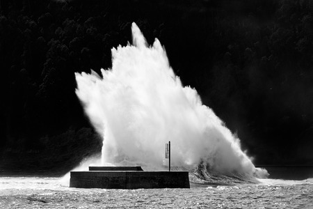 roaring sea: stormy weather on sea with big wave breaking on breakwater Stock Photo