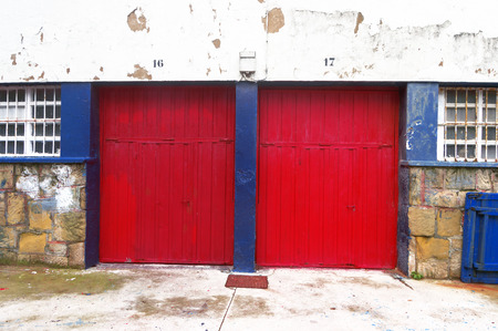 two garages with red roller shutters photo