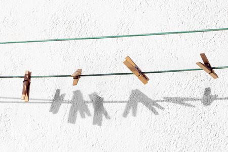 peg for clothes hanging on rope and shadows