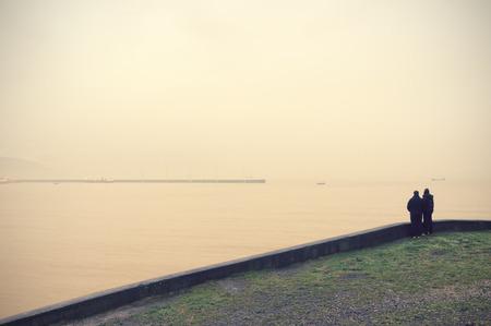 mujer mirando el horizonte: dos personas que buscan en el mar con efecto de filtro de la vendimia Foto de archivo