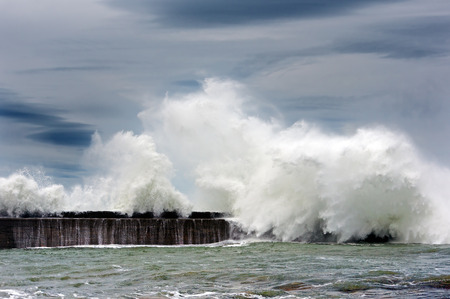 big waves breaking on breakwater with stormy clouds photo