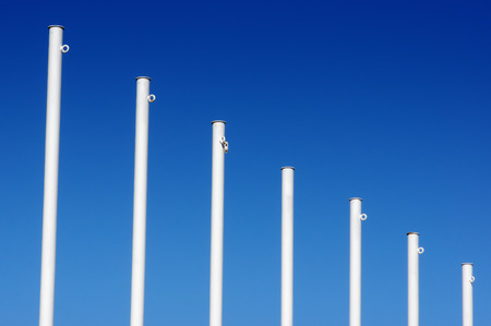 empty white flag poles against blue sky