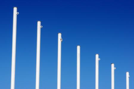 empty white flag poles against blue sky