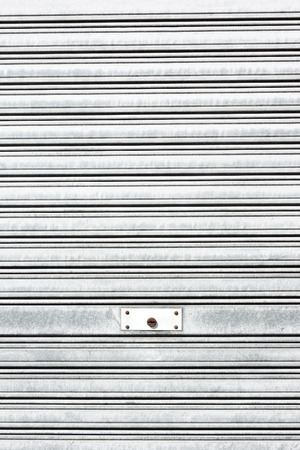 background of metallic roller shutter with door lock photo