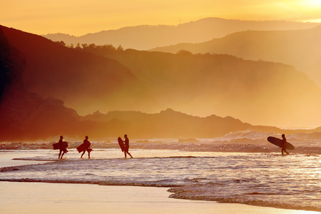 surfing waves: surfers and boogie boards on beach at sunset