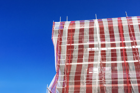 house facade restoration with scaffolding and tarpaulin photo