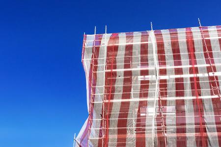 tarpaulin: house facade restoration with scaffolding and tarpaulin