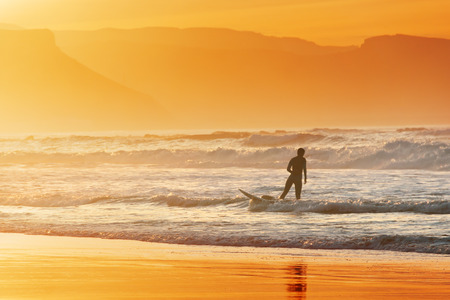 exiting: surfer on shore exiting water at sunset  Stock Photo