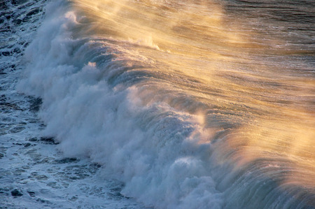 roaring sea: wave breaking with spray at sunset Stock Photo