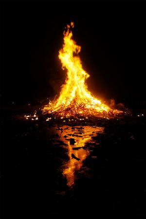 san juan bonfire at night with reflections