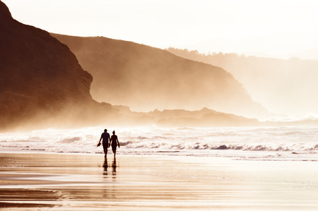 basque woman: couple walking on the beach with fog