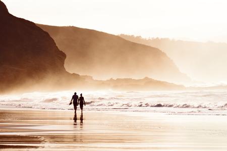 persona caminando: pareja caminando en la playa con niebla
