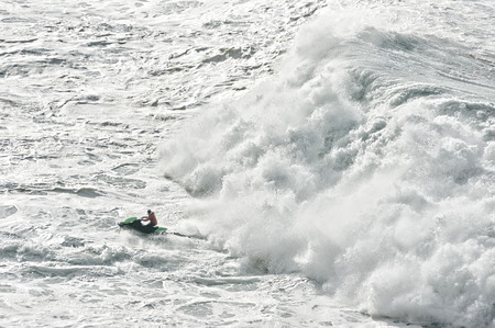 watercraft: watercraft escaping from a huge wave breaking Stock Photo