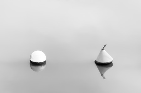 water black: Difference concept. buoys floating on water. Black and white Stock Photo