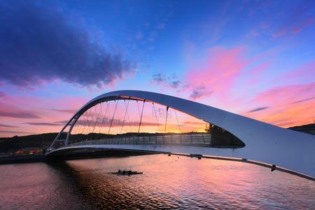 Plentzia bridge at sunset with oarsmen crossing