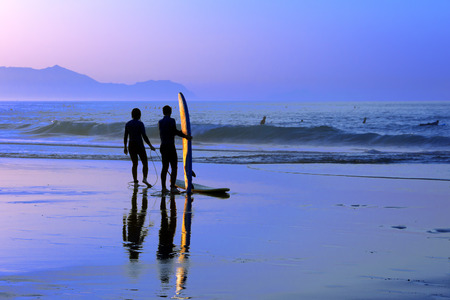 surfers with sunset reflection on the surfboard